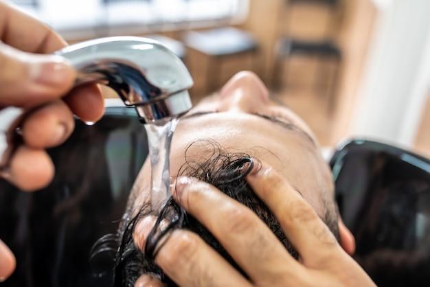 男は理髪店で洗った髪を取得します。 Premium写真