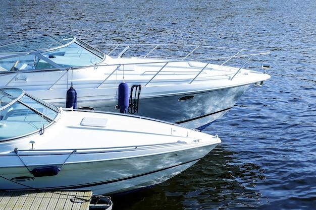 水の上の近代的なモーターボート。桟橋で水に係留 Premium写真