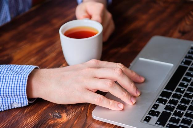 Мужчина пьет чай во время работы за ноутбуком. концепция отдыха во время работы. Premium Фотографии