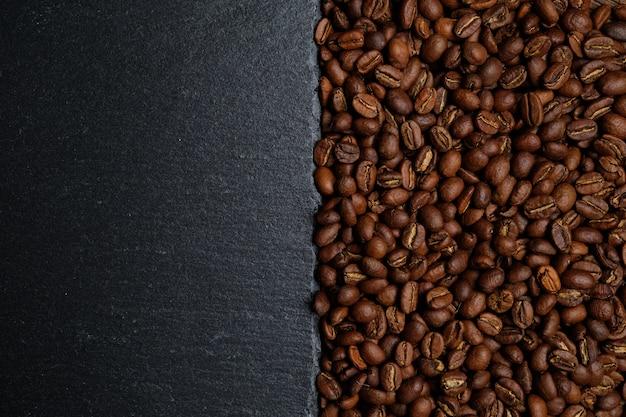 Предпосылка от кофейных зерен и шифера для космоса экземпляра. вид сверху. Premium Фотографии