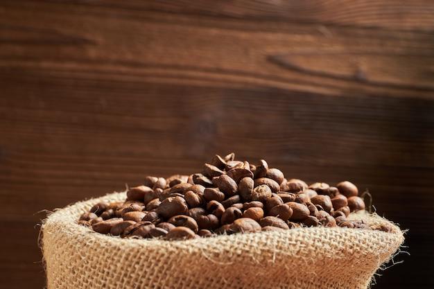 Вязаная сумка с кофейными зернами на фоне обожаемый деревянный фон. копировать пространство Premium Фотографии
