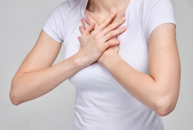 Женщина в белой футболке страдает от боли в груди. затрудненное дыхание. Premium Фотографии