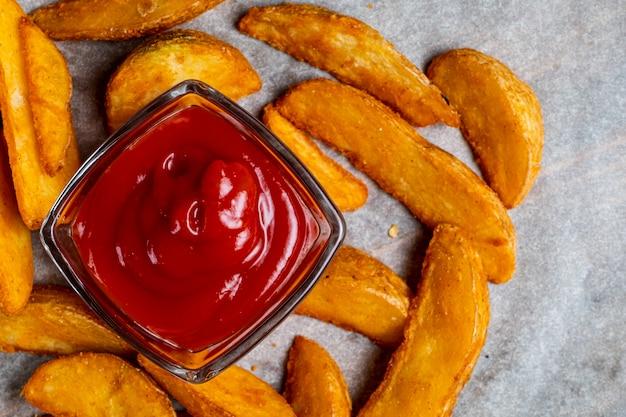 Деревенский жареный картофель на фоне бумаги с кетчупом. вид сверху. Premium Фотографии
