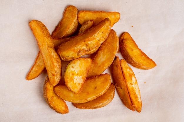 Деревенская картошка на бумажной предпосылке. вид сверху. Premium Фотографии