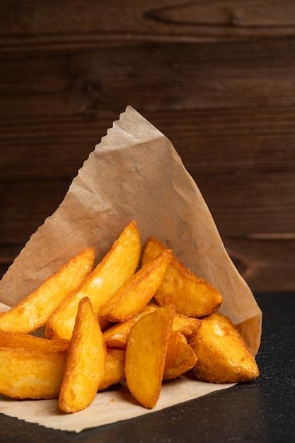 Картофель деревенский посуда шифер, черный камень на деревянном фоне. Premium Фотографии