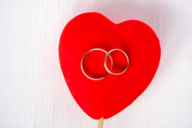 白い背景の上の赤いベルベットのハートのペア結婚金の指輪。オーバーヘッドショット Premium写真