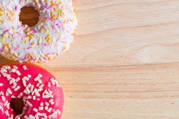 木の上の白とピンクの艶をかけられたドーナツ Premium写真