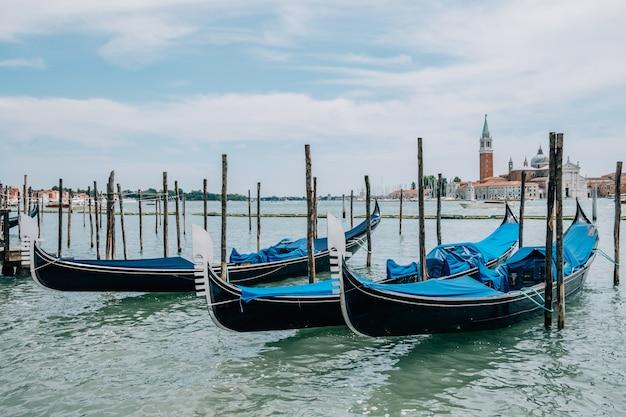 Припаркованные гондолы на воде летом. Premium Фотографии