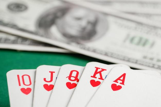 緑のテーブルにドルでポーカー中にハートカードのロイヤルフラッシュ。 Premium写真