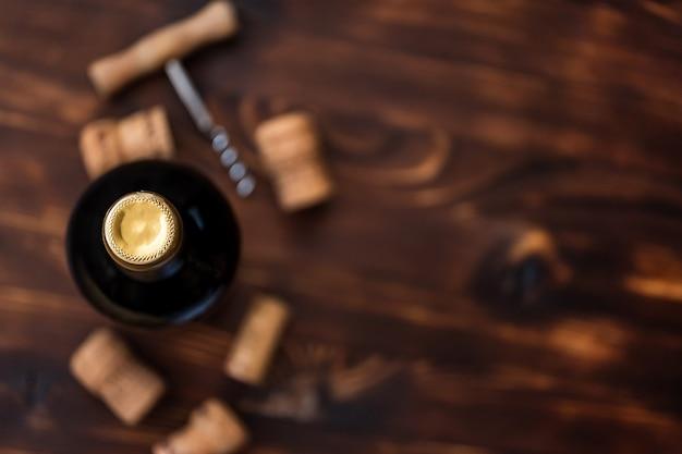 コルク栓抜きと木製のテーブルの上のコルク栓をぼやけの横にあるワインの暗い瓶 Premium写真
