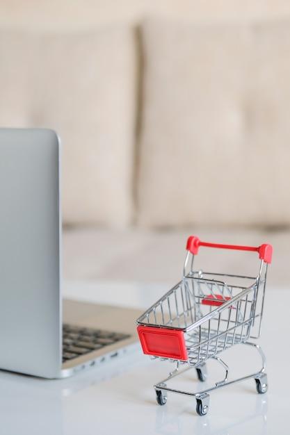 Серый ноутбук на столе рядом с корзиной из супермаркета. вертикальная. Premium Фотографии