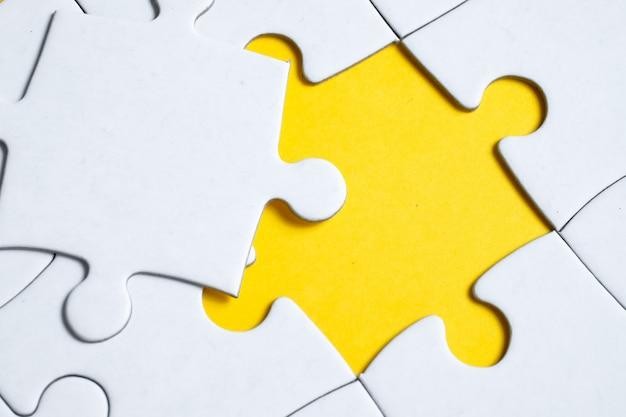Последний отсутствующий белый кусок лежит на мозаике на желтом. Premium Фотографии