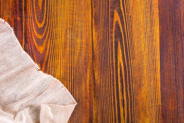 木製のテーブル背景に黄麻布の質感。 Premium写真