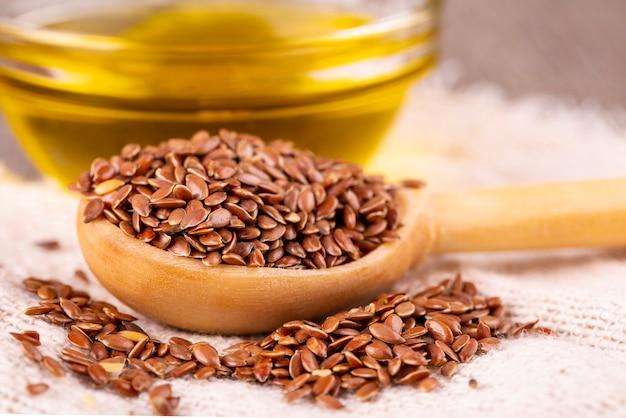茶色の亜麻の種子と木の表面に亜麻仁油 Premium写真