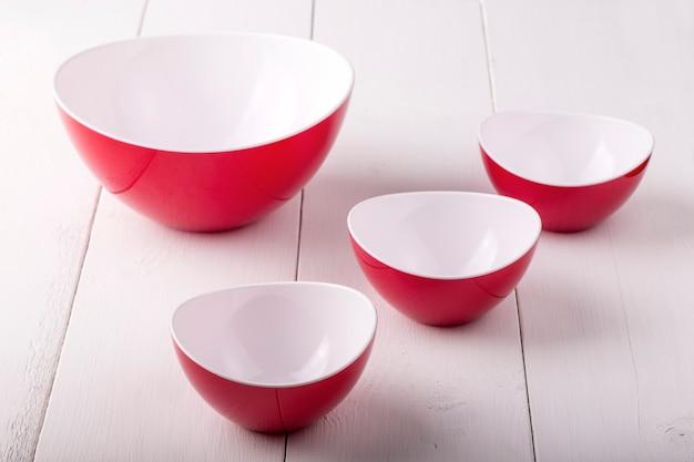 Пустой красный салатник и чашки на белом деревянном столе Premium Фотографии