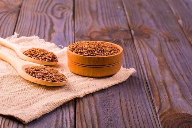 Коричневые семена льна или семена льна в небольшой миске на увольнение и две деревянные ложки на коричневом деревянном столе Premium Фотографии