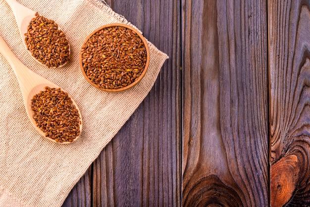 Коричневые семена льна или семена льна в небольшой миске на увольнение Premium Фотографии