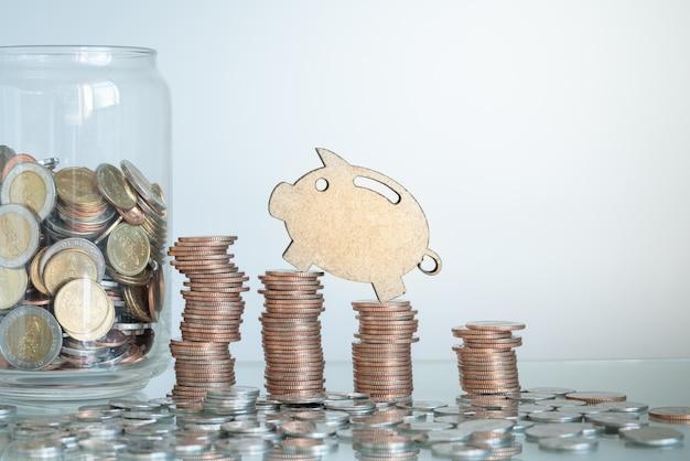 Мини фигура копилка восхождение на стопки монет с монетами в стеклянной банке. бизнес и концепция сбережений. Premium Фотографии