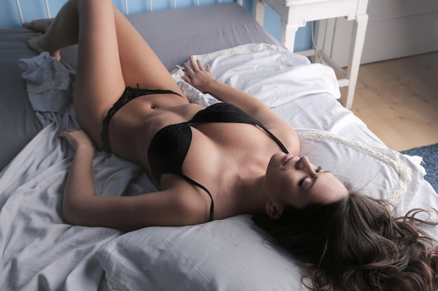 Привлекательная женщина в нижнем белье на кровати Premium Фотографии
