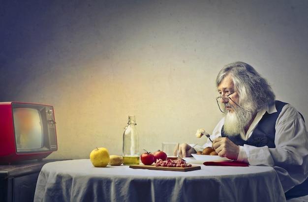 テレビを見て悲しい老人 Premium写真
