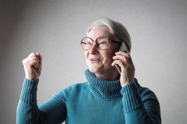 電話で話している幸せの年配の女性 Premium写真