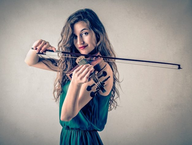 バイオリンで遊ぶ若いきれいな女性 Premium写真