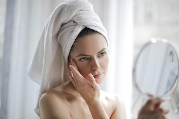 鏡を持つ美しい女の子 Premium写真
