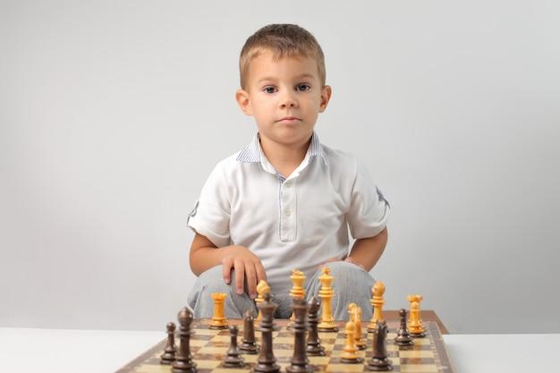 Маленький мальчик играет в шахматы Premium Фотографии