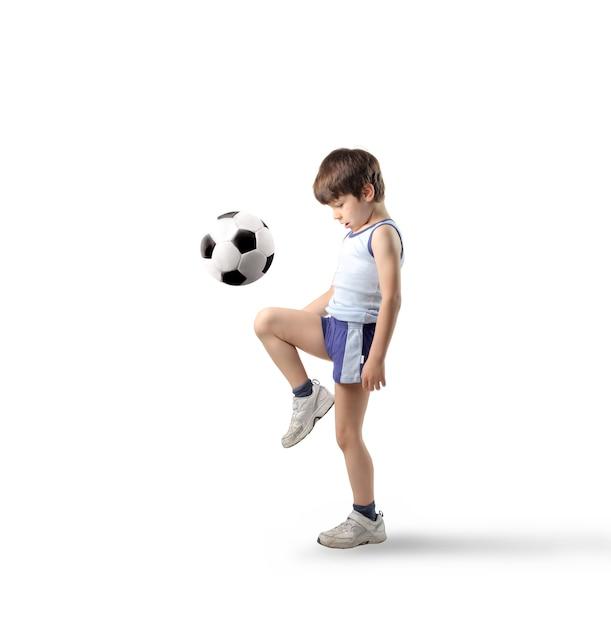 Маленький мальчик играет с футбольным мячом Premium Фотографии