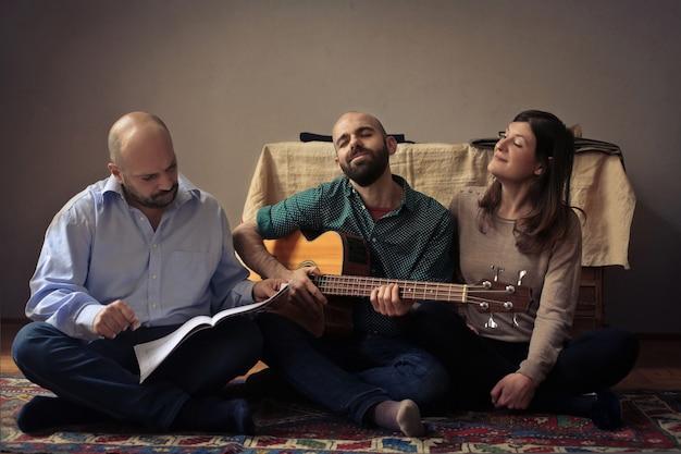 ギターの練習を楽しんでいる大人の友達 Premium写真