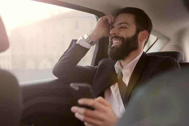 ひげを生やしたビジネスマンが車の中で旅行 Premium写真