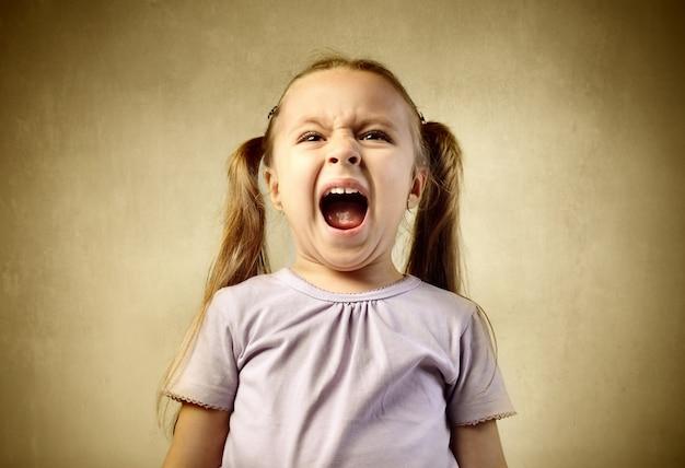 叫んで叫んでいる小さな女の子 Premium写真