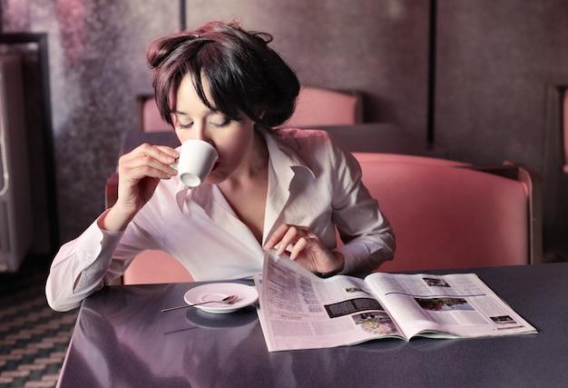 コーヒーを飲みながら雑誌を読む女 Premium写真