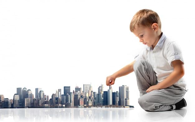 Маленький мальчик играет с городской макет Premium Фотографии