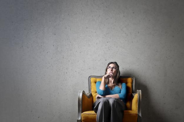 女性は肘掛け椅子について考える Premium写真