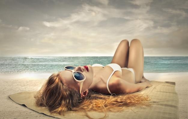 美しい女性の日光浴 Premium写真
