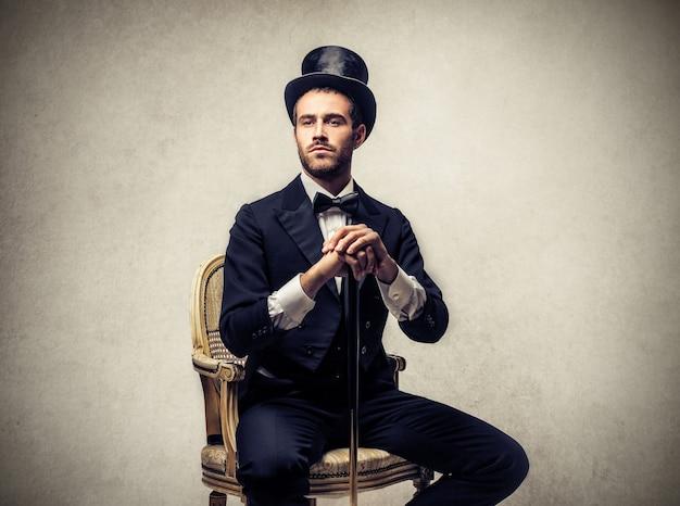 Элегантный мужчина в цилиндре и сидя на стуле Premium Фотографии