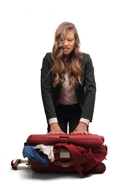 Сердитая женщина упаковывает чемодан Premium Фотографии