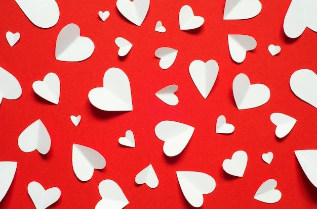 バレンタインデーのロマンチックな背景。白地に赤い背景、ハート型の心。 Premium写真