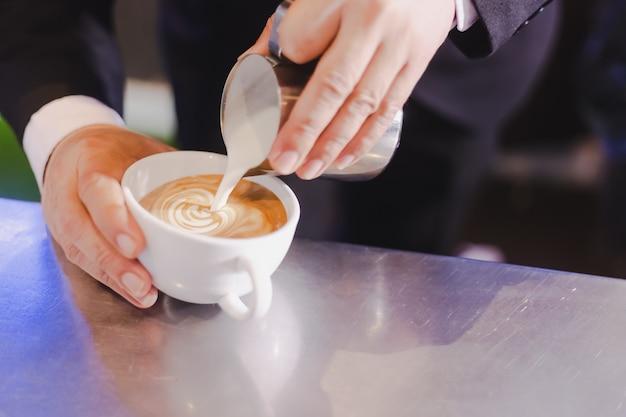 コーヒーの泡とラテアートのためのミルク Premium写真