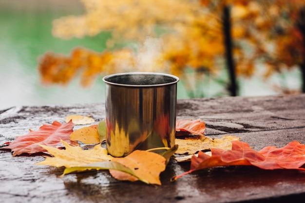 木製のテーブルの上の鋼鉄コップで熱い飲み物。 Premium写真