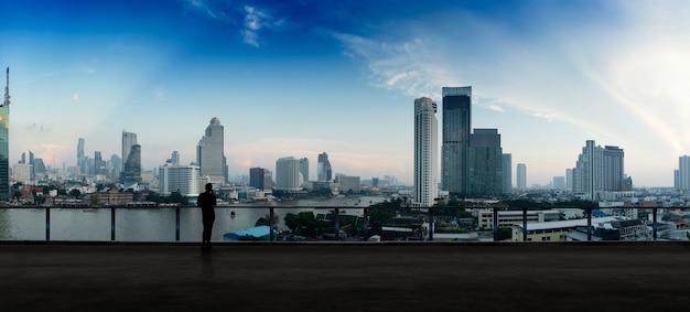 Бизнесмен стоя используя умный телефон на балконе верхней крыши открытой крыши наблюдая взгляд ночи города. бизнес с амбицией и зрением. Premium Фотографии