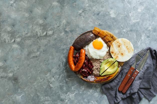 コロンビア料理。バンデハパイサ、コロンビアのアンティオキア地域の代表的な料理-揚げ豚バラ肉、黒プリン、ソーセージ、アレパ、豆、揚げたオオバコ、アボカドの卵、ご飯。 Premium写真