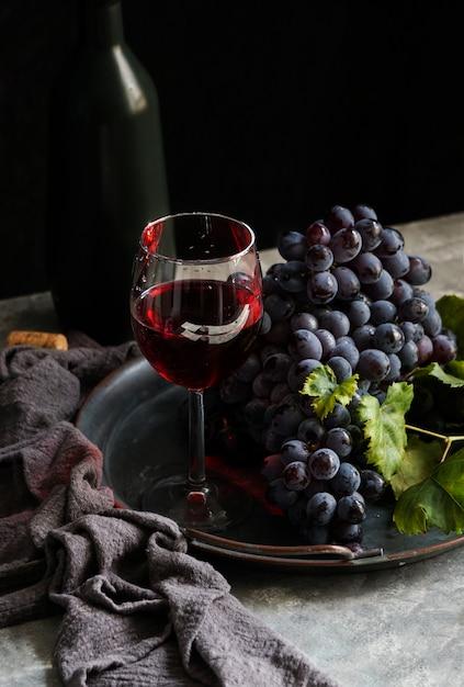 低光、赤ワイン、コピースペースと暗い写真で水滴とブドウの暗い束 Premium写真