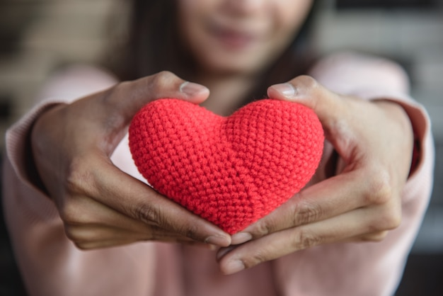 大きな赤い糸の心を持って女性の手で前面に与えます。 Premium写真