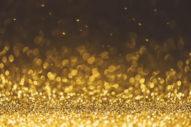 ゴールドラメの輝きライトバックグラウンド。デフォーカスキラキラ抽象的なきらめく光と光沢 Premium写真