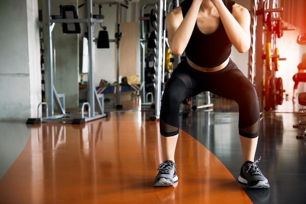 フィットネススポーツジムで脂肪燃焼と足の強さのためにスクワットトレーニングをやっているフィットネス女性 Premium写真