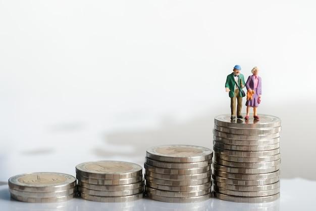 背景退職計画として使用するスタックコインの上に立っている老夫婦の図。 Premium写真