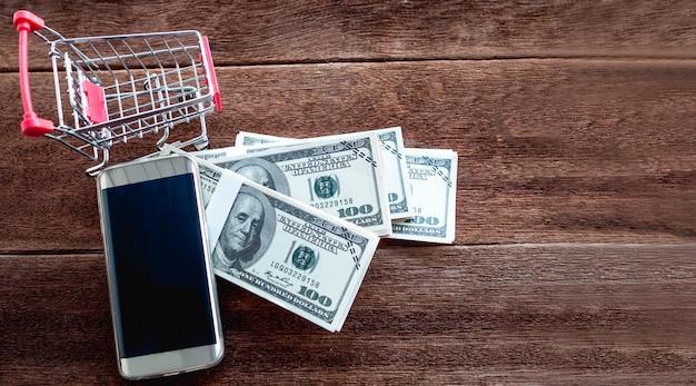 ドルのお金と木製の床に置かれた携帯電話の小さなカートにはコピースペースがあります。オンラインショッピングのコンセプト。 Premium写真