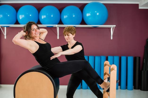 パーソナルトレーナー監督女性ピラティスはしごバレルストレッチ Premium写真